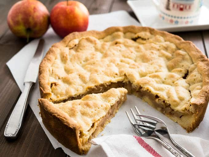 Covered German Apple Cake is one of the best apple cakes! Filled with cinnamon-seasoned apple chunks and topped with a vanilla shortbread crust. You can get this cake in every German bakery!
