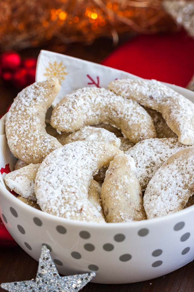 Vanillekipferl (German Vanilla Crescent Cookies) are traditional German Christmas Cookies made with ground nuts and dusted with vanilla sugar! They are tender, nutty and melt in your mouth.  A perfect cookie to make ahead that's always a hit.