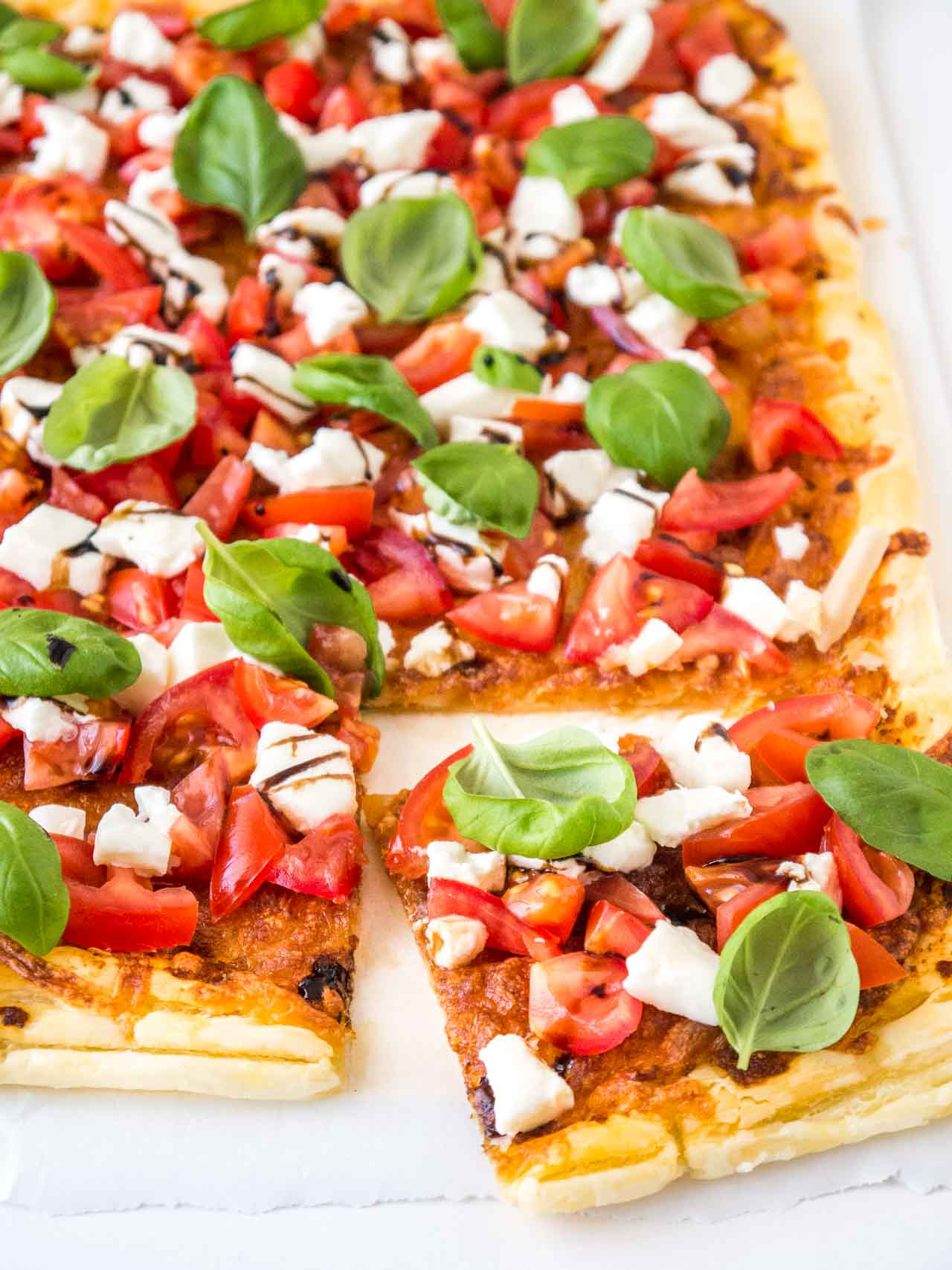 Tomato Mozzarella Puff Pastry Pizza is super easy and fast to make! Crisp pastry brushed with pesto and topped with fresh tomatoes, mozzarella, and basil.