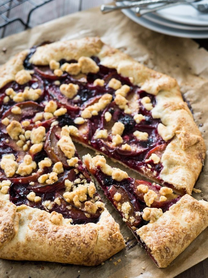 An easy Crostata with Peaches & Berries. Also known as galette, rustic pie or rustic tart. Served with a big dollop of vanilla ice cream, this is my go-to summer dessert!