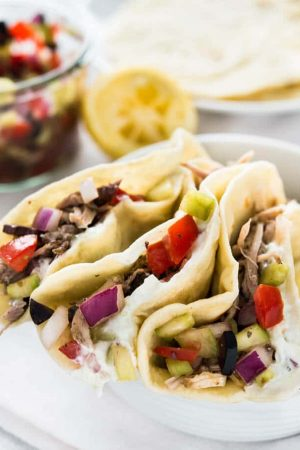 Delicious Greek Tacos with homemade Tzatziki, slow cooker pulled pork Gyros and Greek salsa. Served on homemade flour tortillas! A great twist on normal tacos!