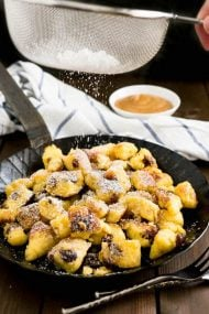 This Kaiserschmarrn recipe is perfect for your Oktoberfest party but it also makes a great dessert for other special occasions! A fluffy pancake made with rum-soaked raisins is torn into bite-sized pieces, caramelized, and served hot sprinkled with Confectioners' sugar.