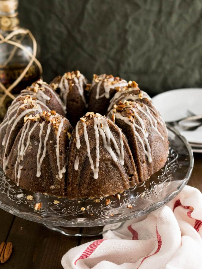 This Pumpkin Bundt Cake is topped with pecans and brushed with a rum glaze while still warm! A great dessert for the holidays which looks impressive but is super easy to make.