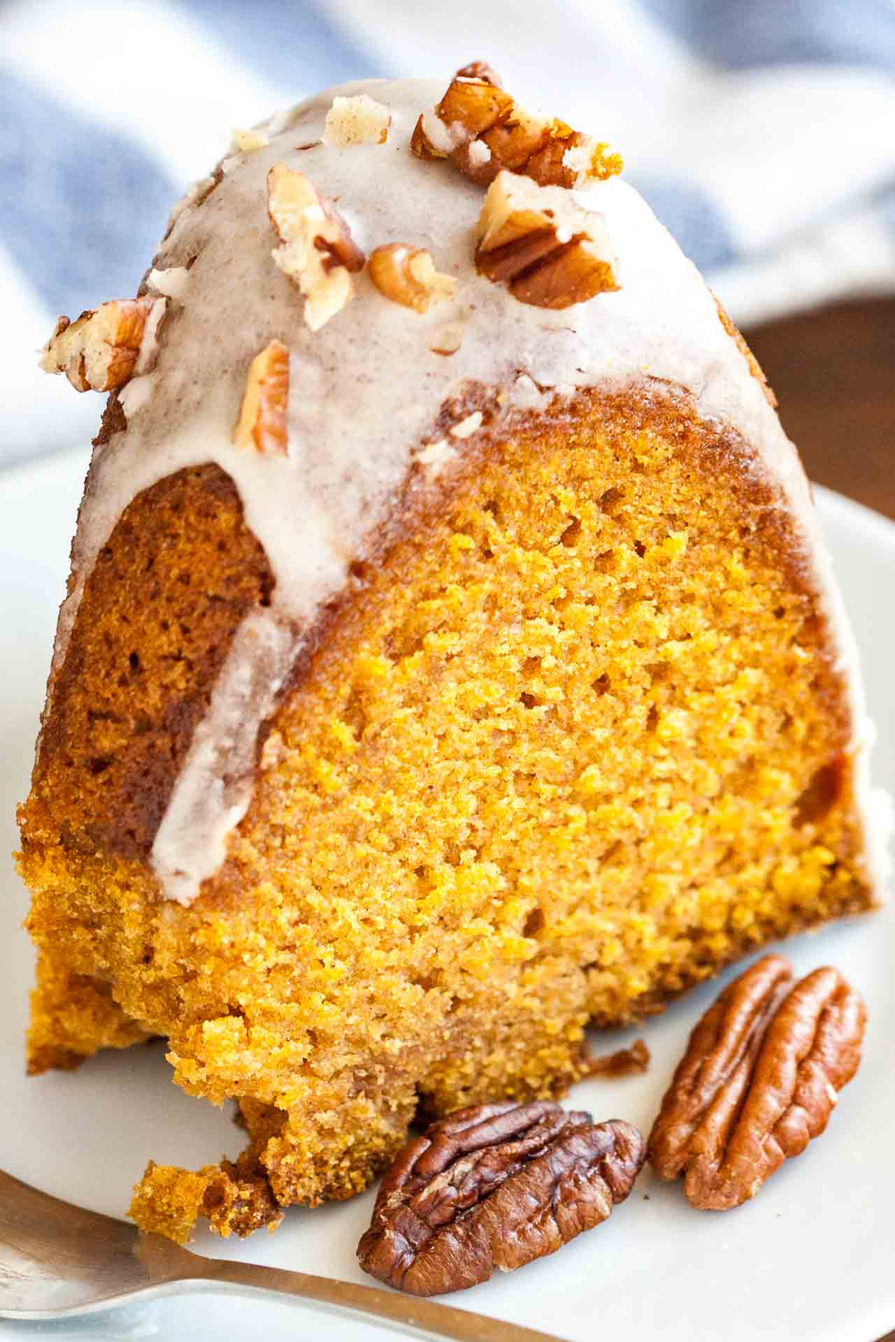 This easy Pumpkin Bundt Cake is topped with a a maple glaze and toasted Pecans! A perfect Thanksgiving dessert.