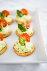 These Feta Tomato Bites are the perfect easy-to-make appetizer for your next party! Made with feta cheese, basil, and topped with a tomato these delicious bites are ready in no time and will sure be a crowd pleaser.