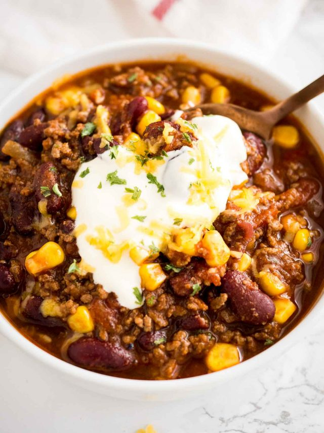 Instant Pot Chili topped with Sour Cream, Shredded Cheese, and Cilantro