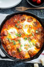 These Italian Baked Eggs and Meatballs are the BEST comfort food! Easy homemade meatballs and sunny side up eggs are simmered in a smooth marinara sauce - a delicious brunch dish that makes a great dinner, too.