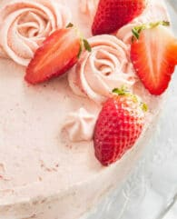 This homemade Strawberry Cake Recipe is bursting with fresh strawberry flavor and made completely from scratch! Layers of soft and fluffy vanilla cake filled with a strawberry buttercream and a layer of fresh strawberry filling. A perfect cake for spring and summer! #strawberrycake #cakefromscratch #strawberry #strawberries #layercake