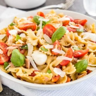 Pasta Salad with Italian Dressing is a must make for any occasion! A summer classic loaded with cherry tomatoes, pine nuts, Italian ham, mozzarella, and fresh basil. Perfect side dish for BBQ parties, potlucks, or as a quick weeknight meal!