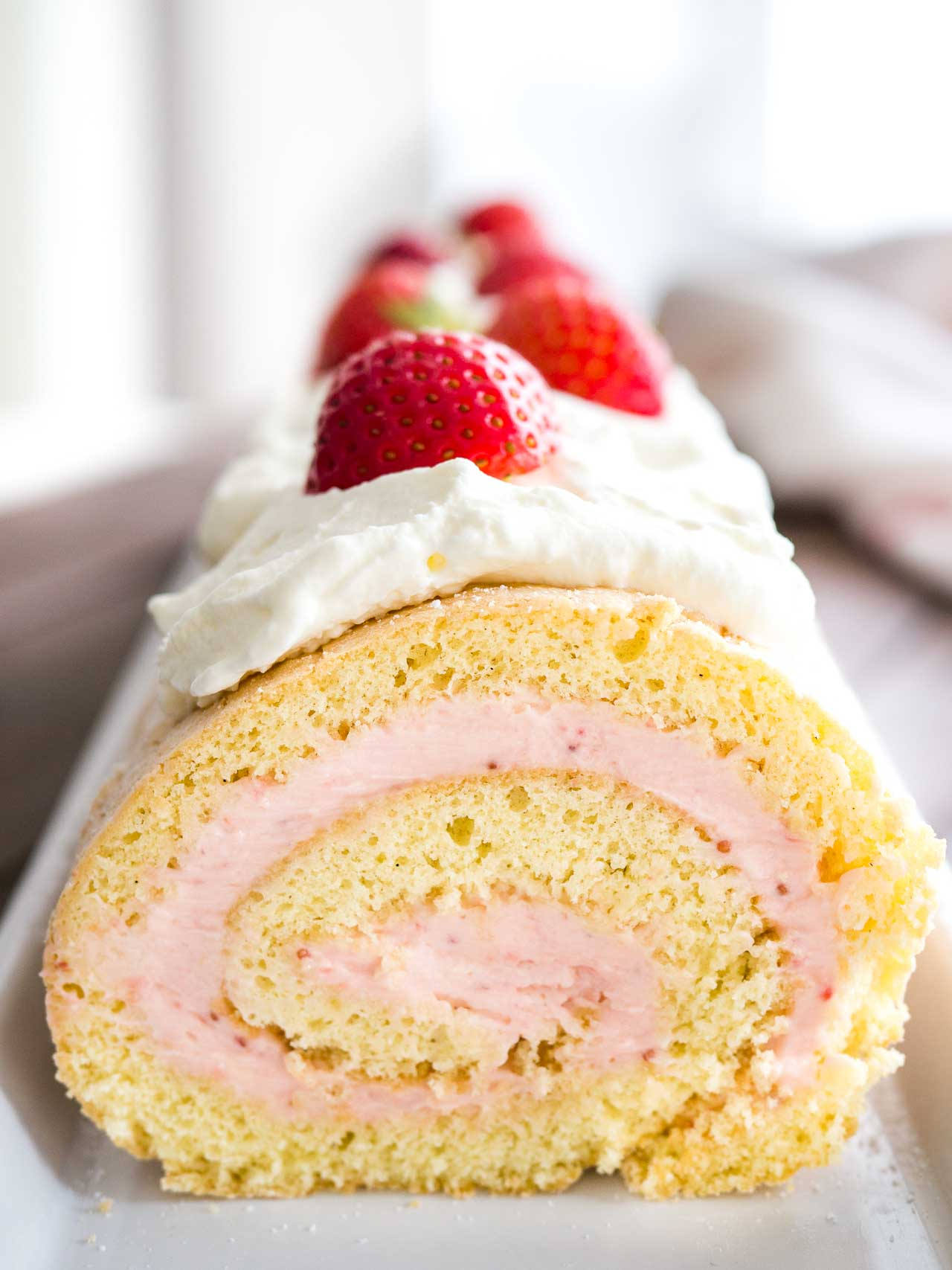 Strawberry Swiss Roll Cake is a light and refreshing cake that's perfect for summer! A fluffy cake roll that is easier to make than you think and tastes so delicious. Perfect for guests and special occasions!