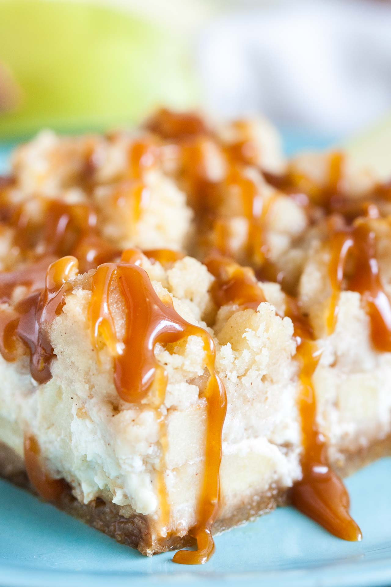 Caramel Apple Cheesecake Bars have three delicious layers and are a perfect fall dessert! A graham cracker crust topped with a creamy cheesecake layer loaded with cinnamon spiced apples and cookie-like streusel and salted caramel on top.