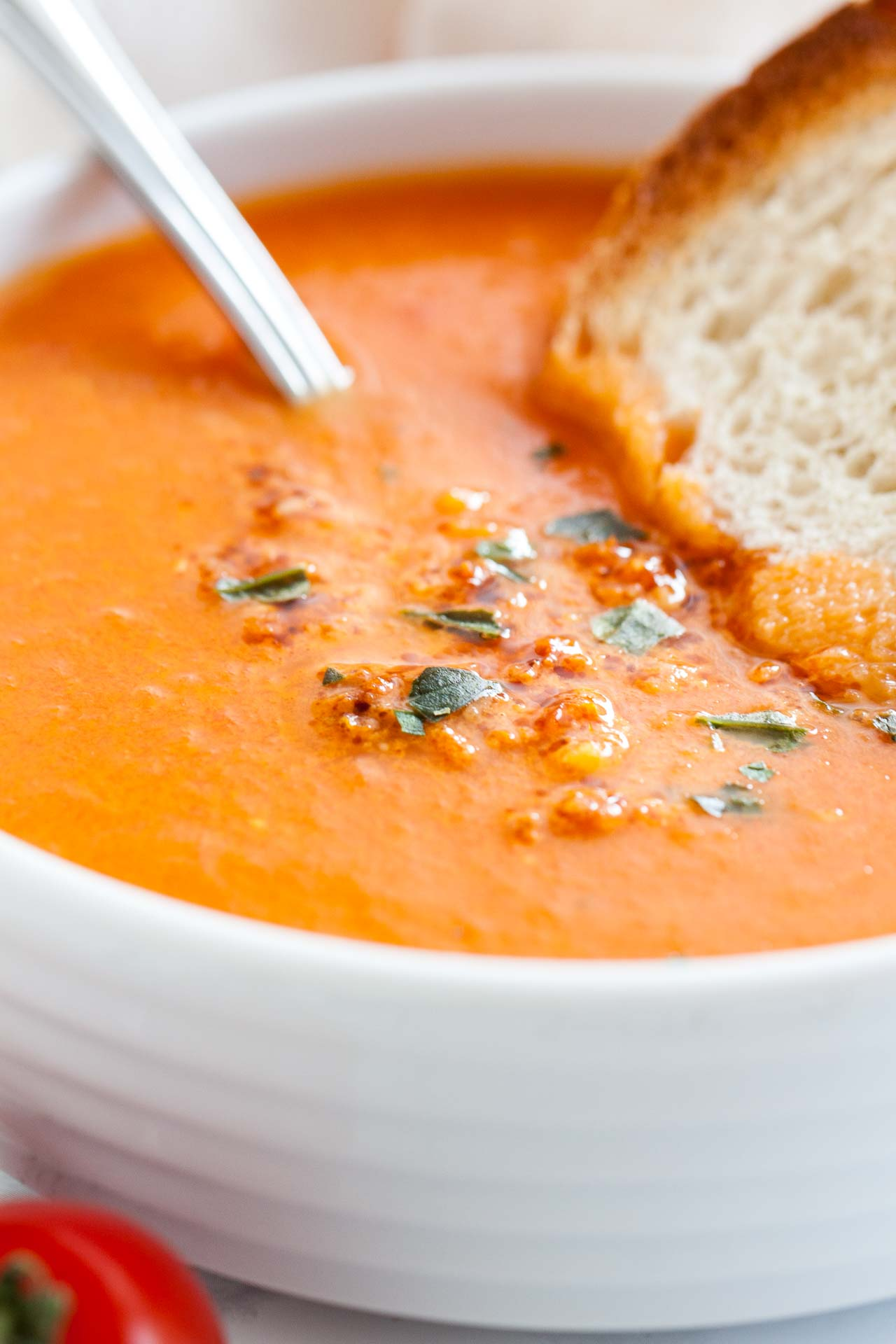 A creamy and healthy Roasted Tomato Soup that's loaded with fresh flavors and super easy to make! This easy tomato basil soup recipe is perfect for a cold winter day, super tasty, and has less than 200 kcal for a big bowl. Serve it with rustic bread or grilled cheese sandwiches for dinner or lunch!