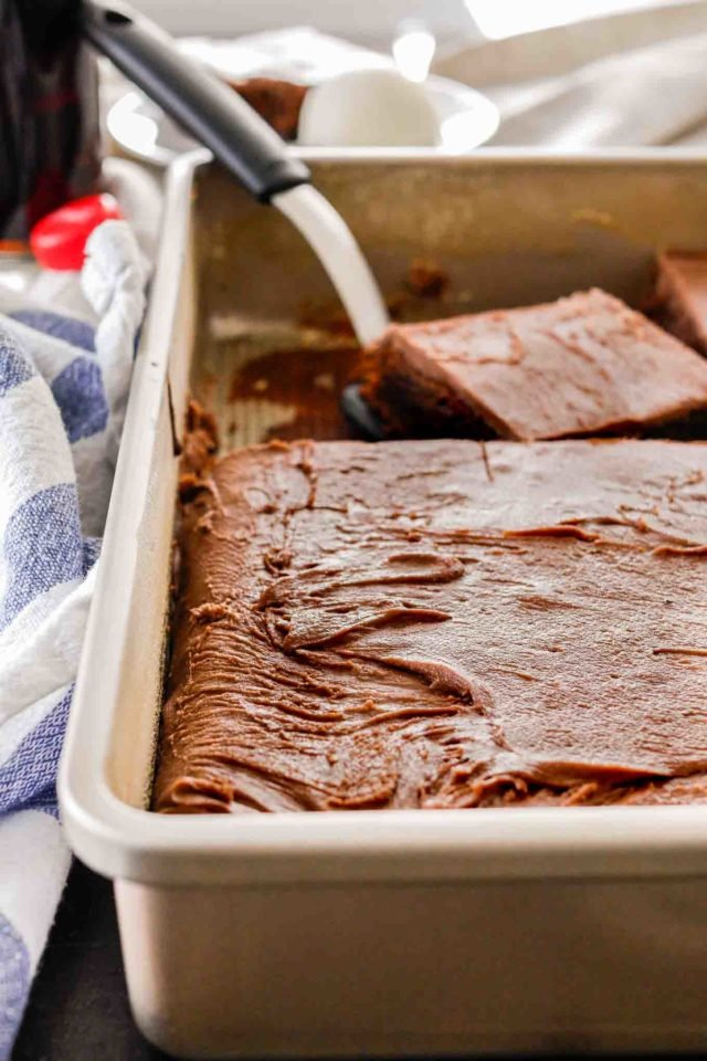 coca cola cake in a baking sheet with a spatula taking a piece out