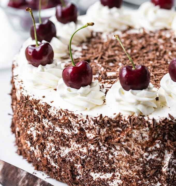 Black Forest Cake. The cake has chocolate shavings on the side and swirls of whipped cream topped with whole cherries on top