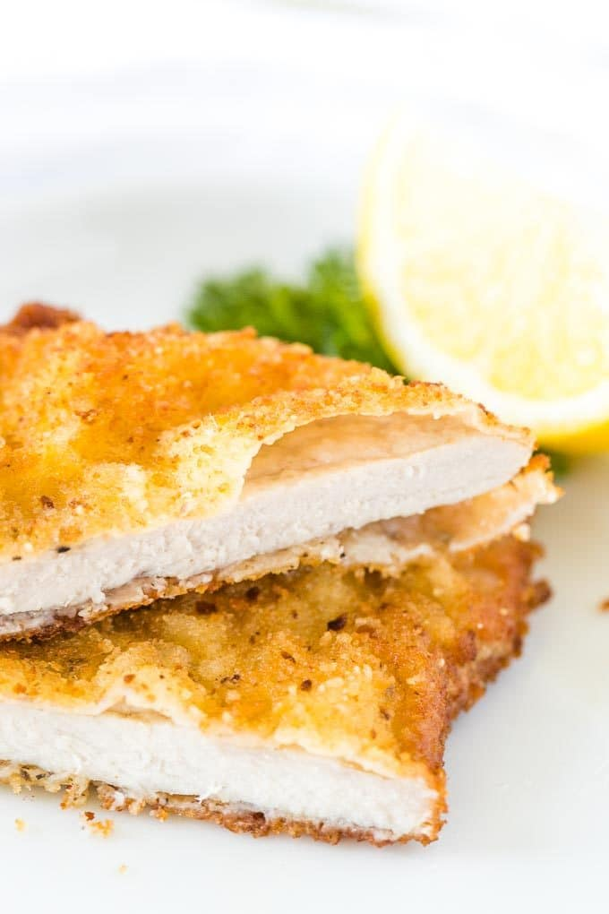 Schnitzel, cut in half, stacked on a plate, garnished with lemon and parsley