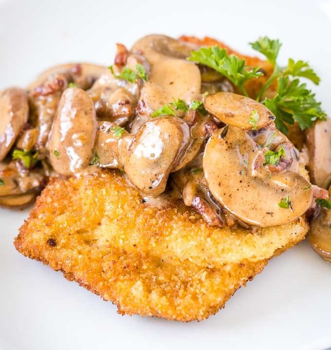 Schnitzel topped with Mushroom, bacon gravy, garnished with parsley