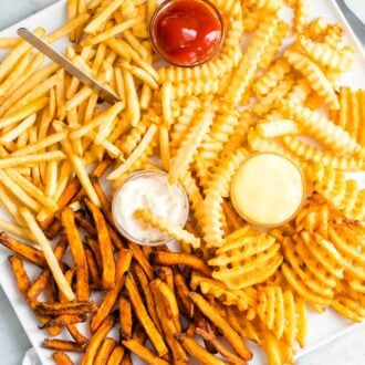 Different french fries on a platter with condiments