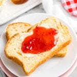 Two slices of bread on a plate with butter and jam spread on top