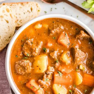 A bowl of beef stew with a spoon and bread next to it
