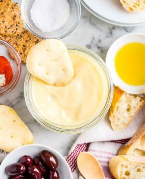 Aioli in a jar with bread and antipasti next to it