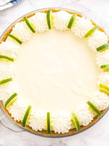 A key lime pie decorated with whipped cream and lime slices