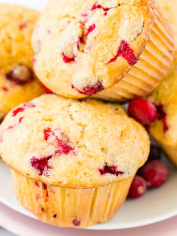 A stack of orange cranberry muffins on a white plate