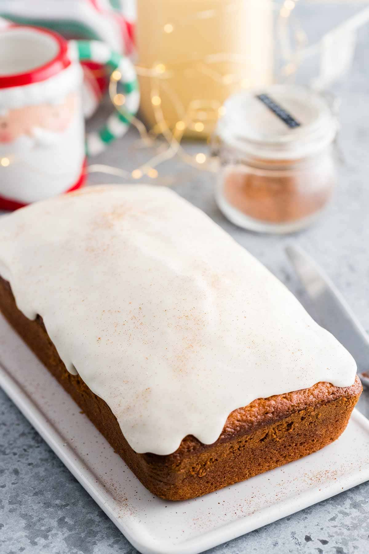 A side shot of an eggnog quick bread with a white glaze and nutmeg on top