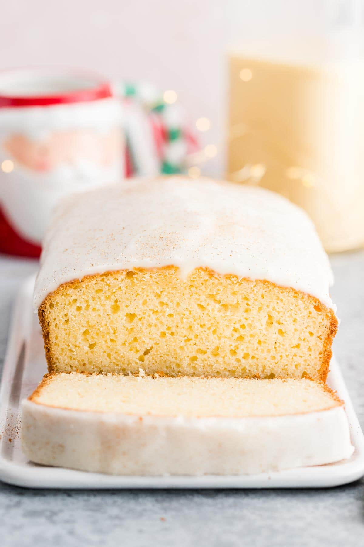 An eggnog loaf cake on a serving platter with a slice in front of it