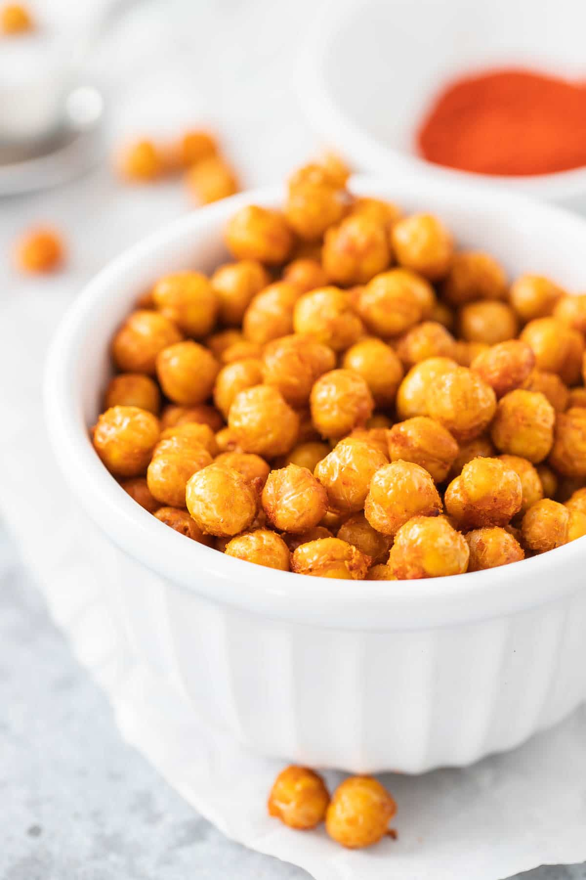 Air fried chickpeas in a white bowl next to a bowl of spices