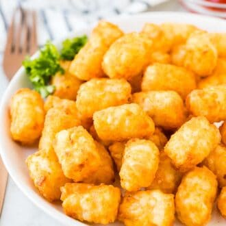 Air Fried Tater Tots on a white plate next to a small bowl of ketchup