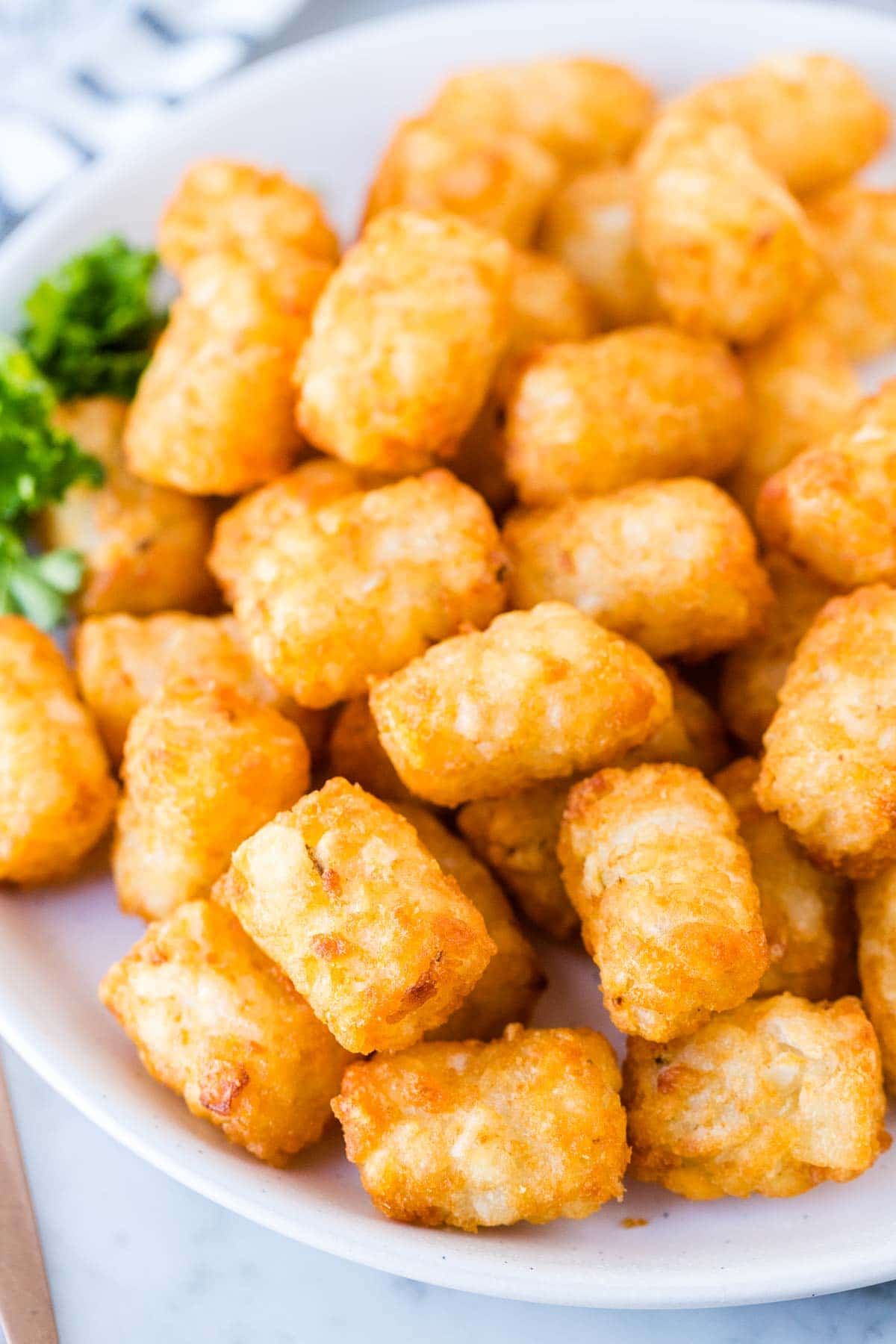 A close up of a plate of crispy tater tots