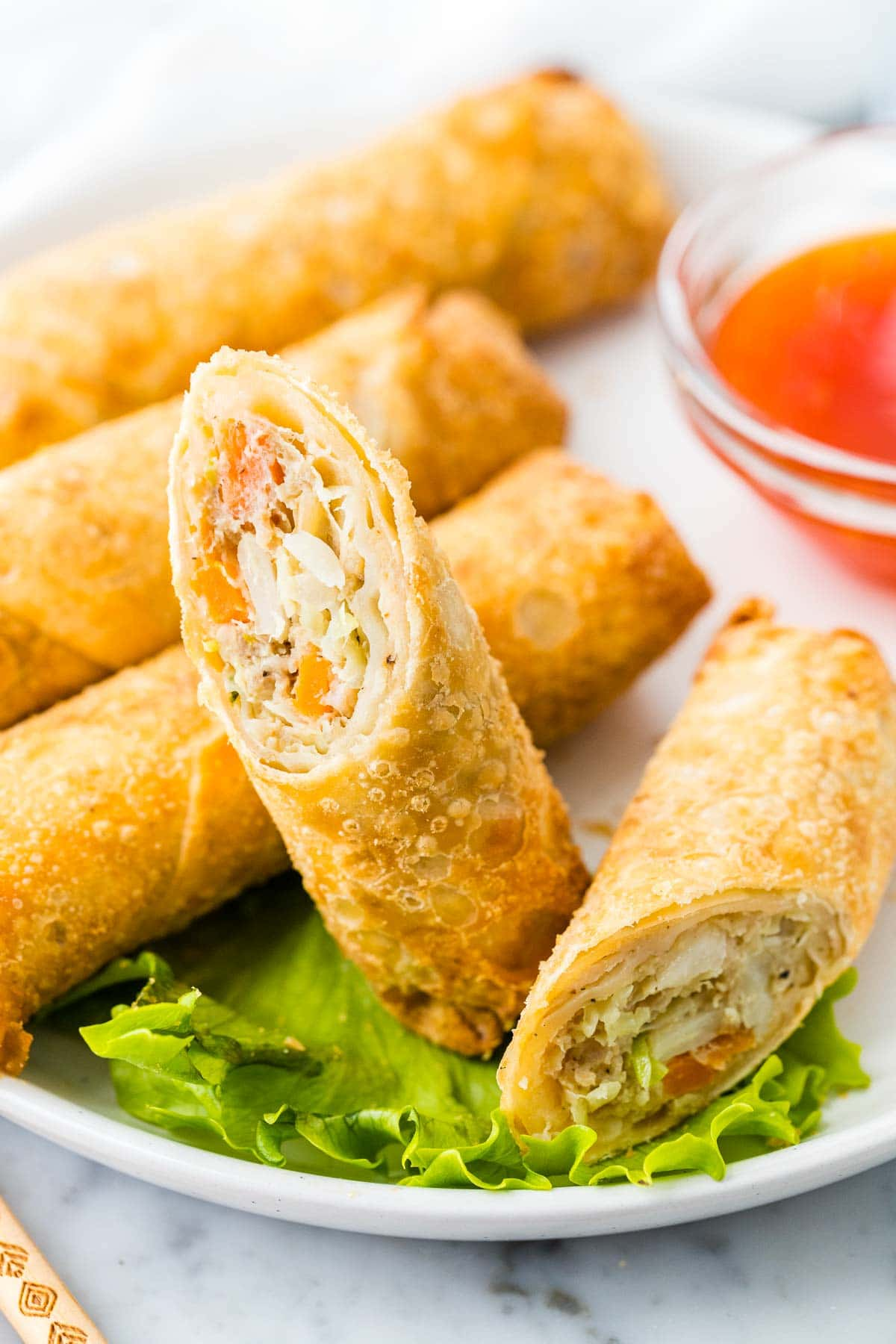 An egg roll cut into two halves on a white plate