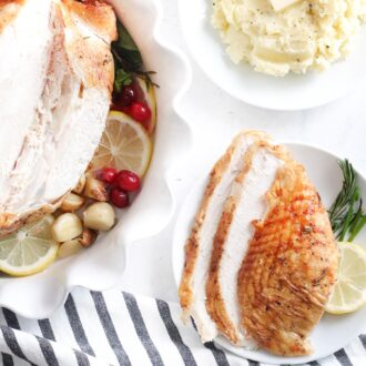 Sliced turkey breast on a plate next to a bowl of mashed potato and a whole turkey breast