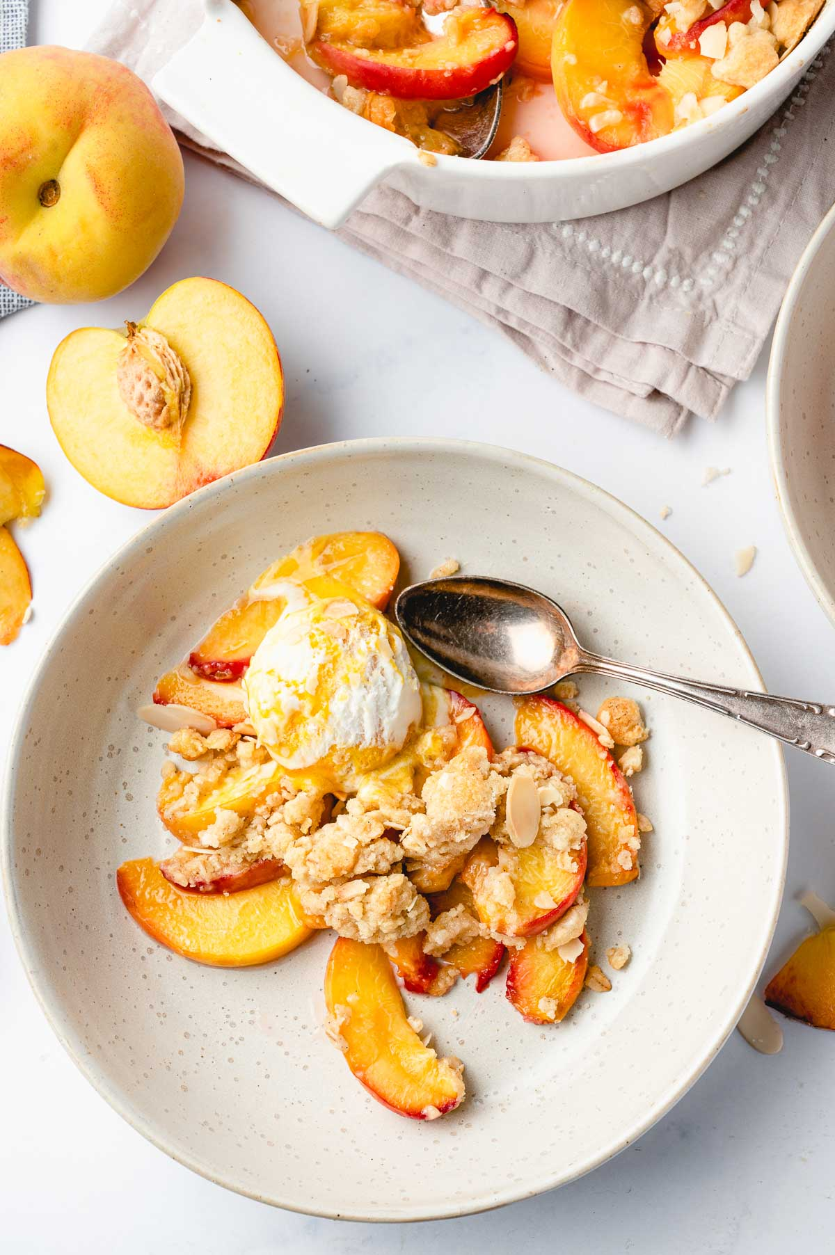 Top down shot of a plate with peaches, topping, and ice cream