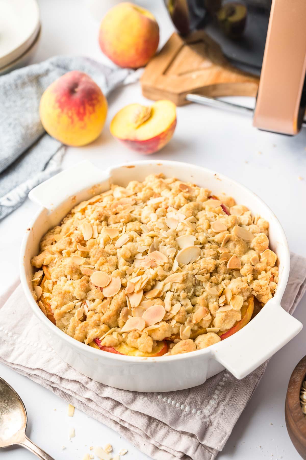 A peach crumble in a baking pan next to some peaches