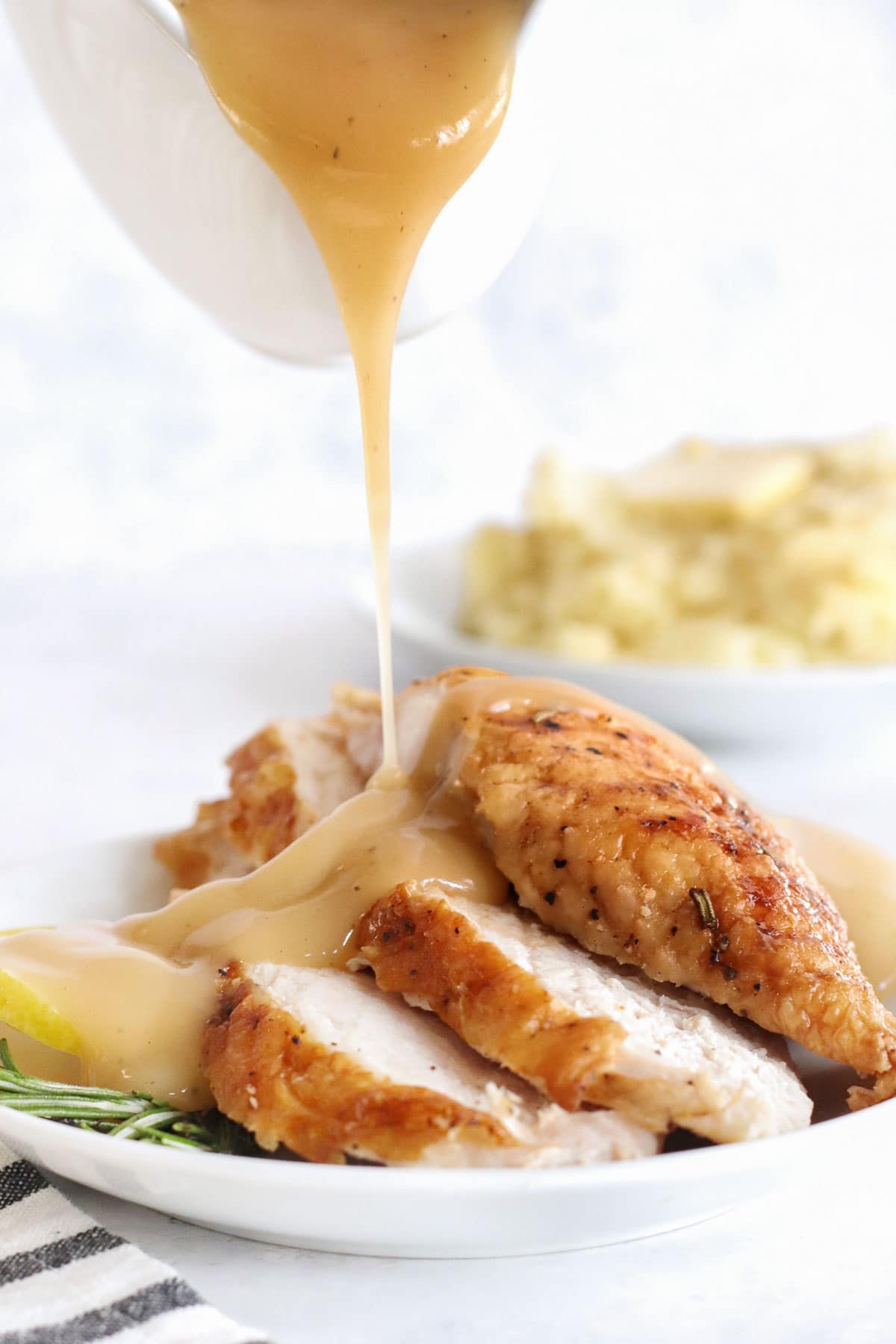 Sauce being poured onto sliced turkey breast on a plate