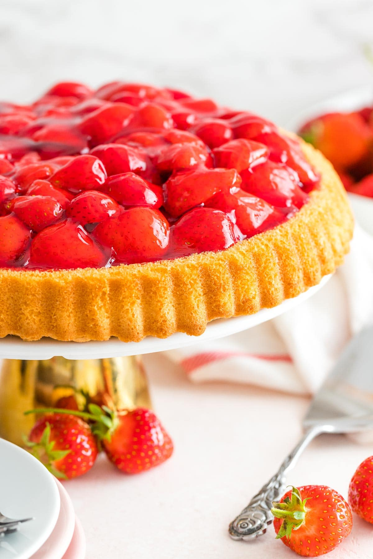 A cake made with strawberries on a cake stand