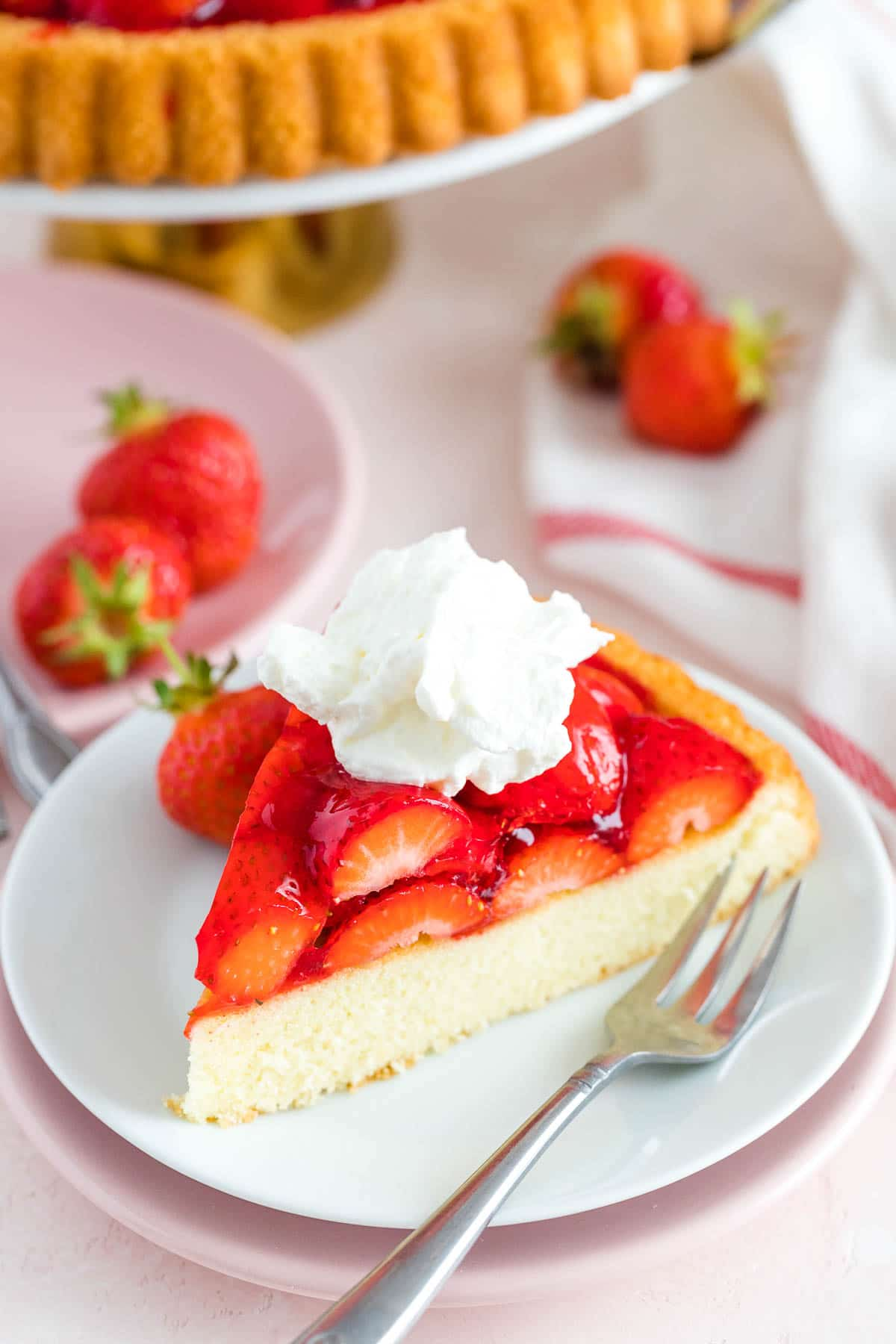 A slice of strawberry cake on a plate with a fork
